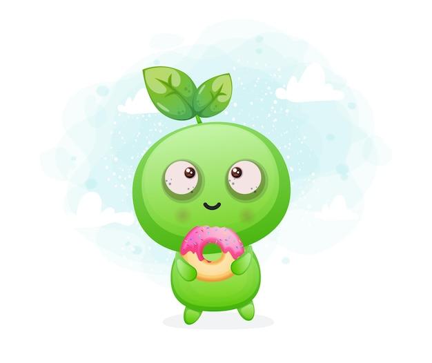 Netter glücklicher lächelnder samen, der donut alien-maskottchencharakter hält premium-vektor