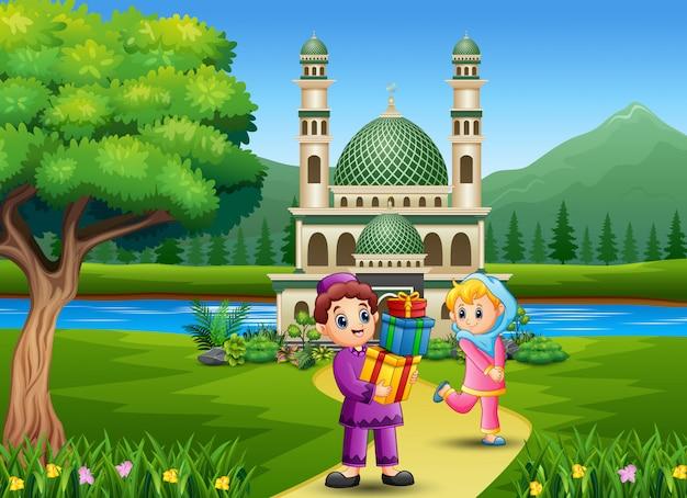 Netter islamischer junge, der dem mädchen in der front die moschee geschenke gibt
