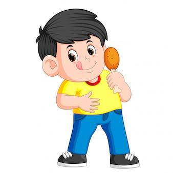 Netter junge, der ein frittiertes huhn isst