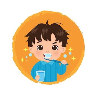 Netter junge, der ein glas hält und seine zähne mit zahnbürste putzt