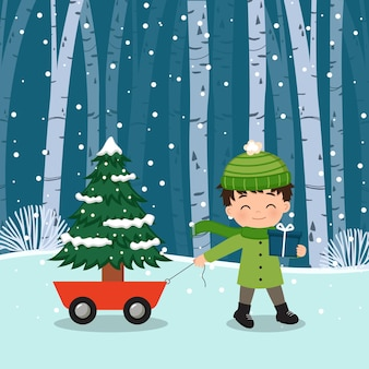 Netter junge, der einen wagen mit weihnachtsbaum zieht, während er eine geschenkbox hält
