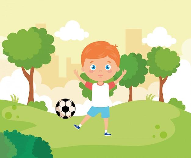 Netter junge im park mit fußball