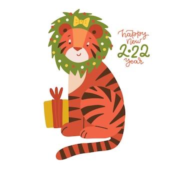 Netter karikaturgestreifter roter tiger mit geschenkbox und weihnachtskranz auf seinem kopf lustiges baby tiger sym...