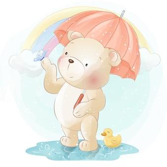 Netter kleiner bär, der regenschirm hängt