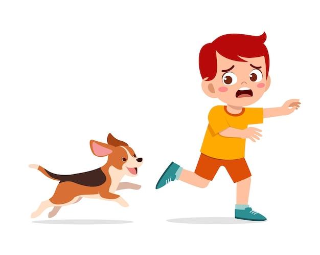 Netter kleiner junge, der angst hat, weil er von einem bösen hund verfolgt wird