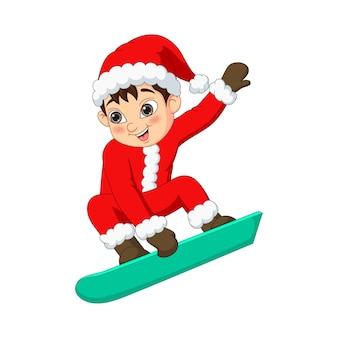 Netter kleiner junge, der ein snowboard spielt