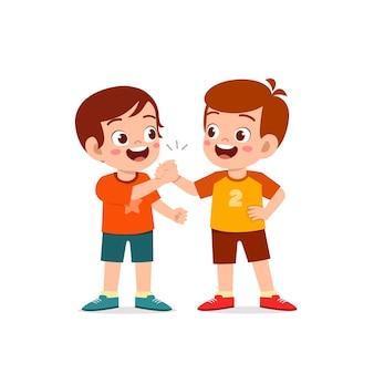 Netter kleiner junge, der hand mit seinem freund hält