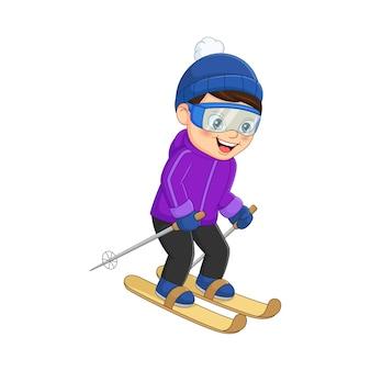 Netter kleiner junge, der in der winterkleidung ski fährt