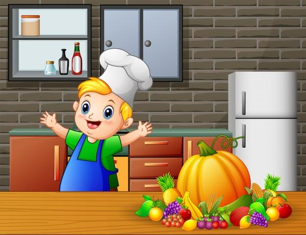Netter kleiner junge der karikatur im schutzblech und hut des chefs nahe speisetische