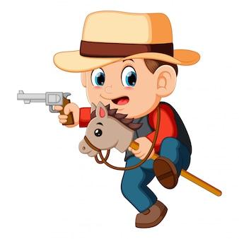 Netter kleiner junge, der mit einem pferd auf einem stock- und gewehrspielzeug spielt
