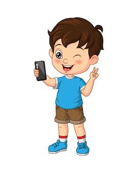 Netter kleiner junge, der selfie mit einem smartphone macht