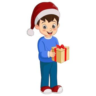 Netter kleiner junge, der weihnachtsgeschenk hält