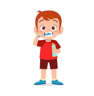 Netter kleiner junge, der zähne putzt und zahnpasta hält