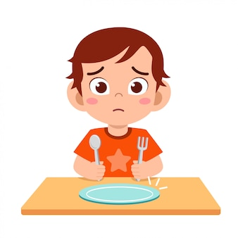 Netter kleiner junge fühlt sich hungrig essen wollen