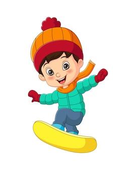 Netter kleiner junge in winterkleidung, der ein snowboard spielt