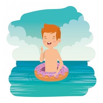 Netter kleiner junge mit badeanzug und donut schwimmen auf das meer