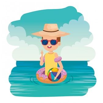 Netter kleiner junge mit donutfloss und strandballon auf dem meer