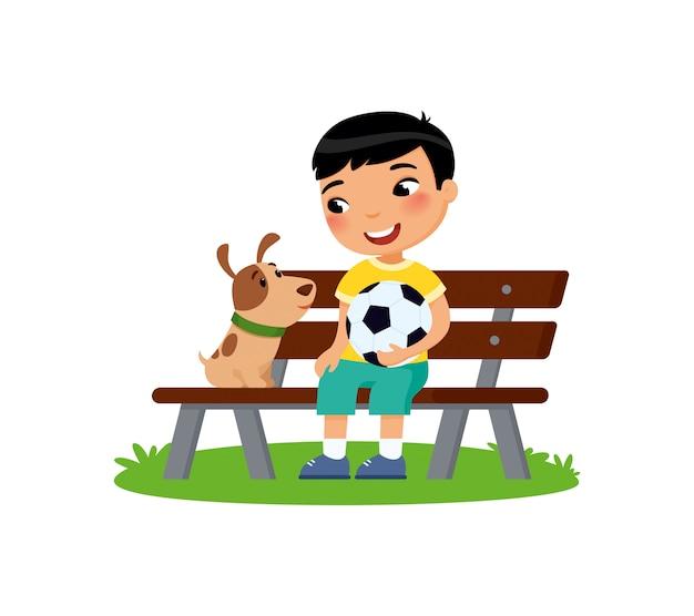 Netter kleiner junge mit fußball und welpe sitzen auf der bank. glückliches schul- oder vorschulkind und ihr haustier, die zusammen spielt.