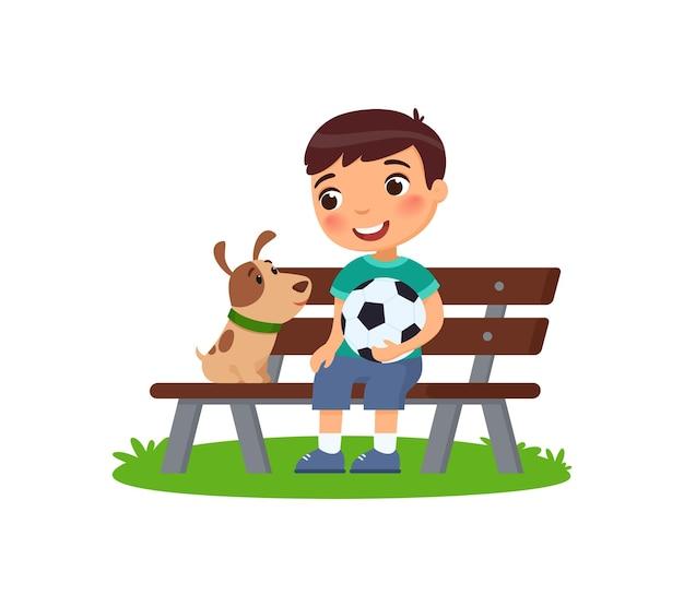 Netter kleiner junge mit fußball und welpe sitzen auf der bank