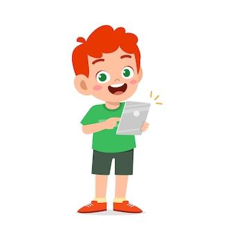 Netter kleiner junge mit smartphone und internet