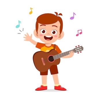 Netter kleiner junge spielt gitarre im konzert