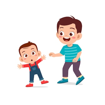 Netter kleiner junge spielt mit babygeschwister zusammen und lernt laufen