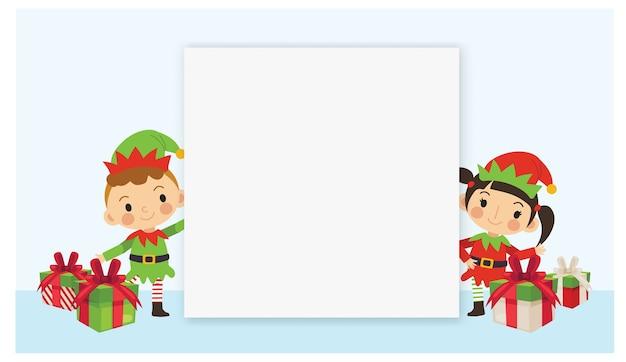 Netter kleiner junge und mädchen im elfenkostüm mit weihnachtsgeschenkboxen und leerzeichenplakat.