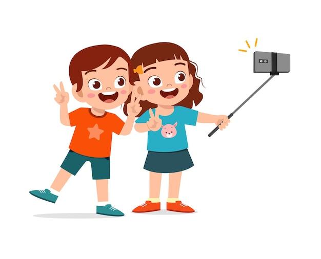 Netter kleiner junge und mädchen nehmen selfie zusammen