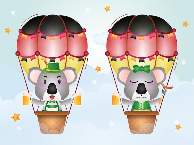 Netter koala auf heißluftballon mit traditionellem oktoberfestkleid