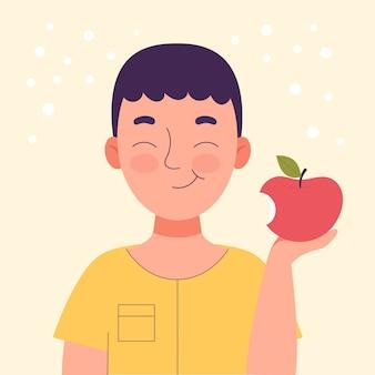 Netter lächelnder junge, der einen apfel isst