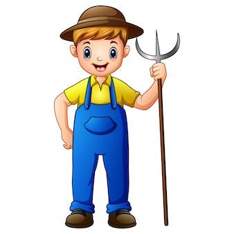 Netter landwirt des jungen kerls, der heugabel hält