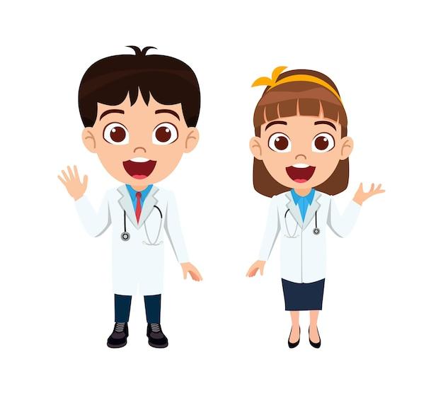 Netter schöner kinderjungen- und -mädchenarzt, der steht und winkt und mit doktorausstattungen zeigt, die mit stethoskop isoliert werden
