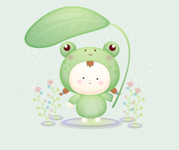 Nettes baby im froschkostüm, das blatt hält. maskottchen-karikaturillustration premium-vektor