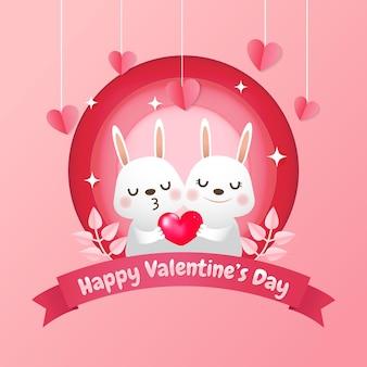 Nettes hasenpaar, das ein realistisches rotes herz hält. valentinstag im papierausschnittstil. pink schön.
