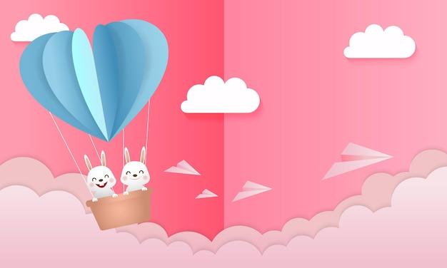Nettes hasenpaar im schönen heißluftballon. origami stil konzept hintergrund. kaninchen zeichentrickfigur verliebt.