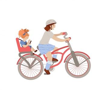 Nettes jugendliches oder jugendliches mädchen, das ein fahrrad mit dem kleinen mädchen auf dem hinteren kinderfahrradsitz, babyträgersitz fährt.