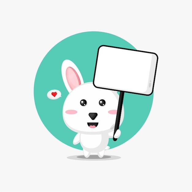 Nettes kaninchen, das ein leeres zeichen hält