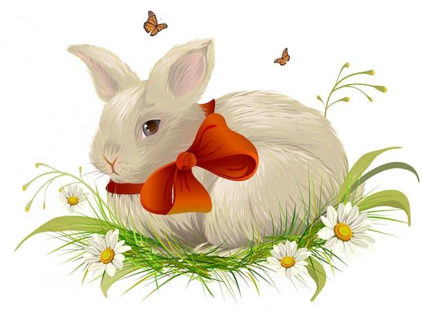 Nettes kaninchen mit dem bogen, der auf gras sitzt. osterhase mit roter schleife