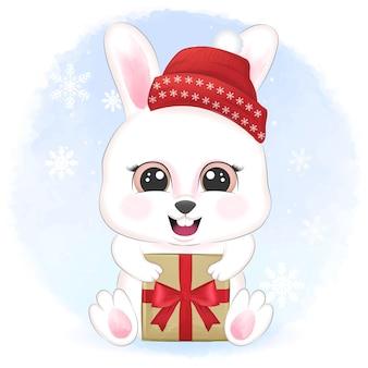 Nettes kaninchen mit geschenkbox in winter- und weihnachtsillustration.