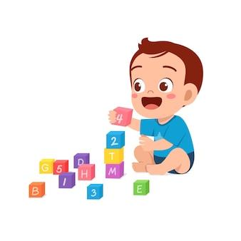 Nettes kleines baby, das mit bunten ziegelsteinen spielt