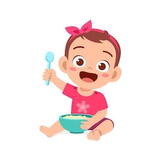 Nettes kleines baby isst brei in schüssel mit löffel