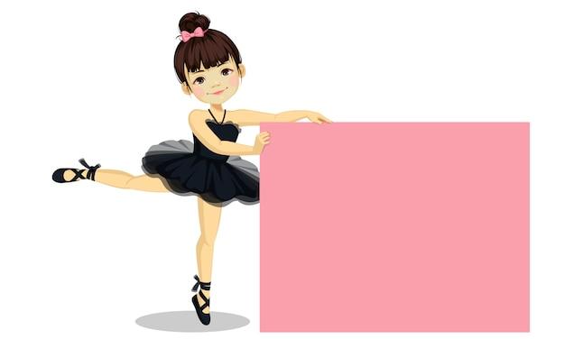 Nettes kleines ballerinamädchen im schwarzen ballettröckchenkleid mit leerem brett