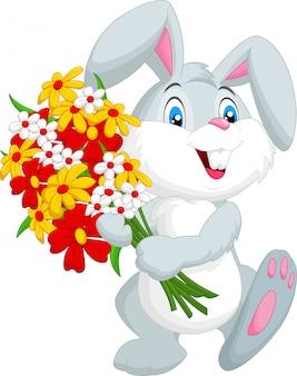 Nettes kleines kaninchen, das einen blumenstrauß anhält