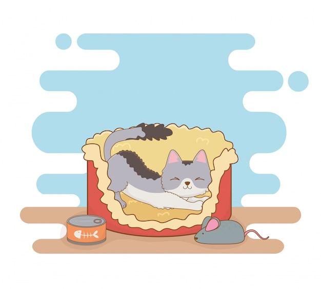 Nettes kleines katzenmaskottchen im bett mit thunfischdose und -maus
