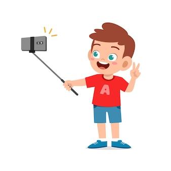 Nettes kleines kind jungenpose und selfie vor der kamera