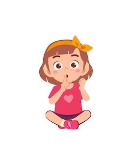 Nettes kleines mädchen zeigt engen mund mit fingerpose
