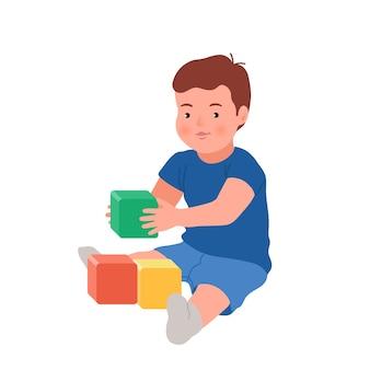 Nettes lächelndes kind, das mit bunten würfeln spielt. baby spielt entwicklungsspielzeug. spielzeug für kleine kinder