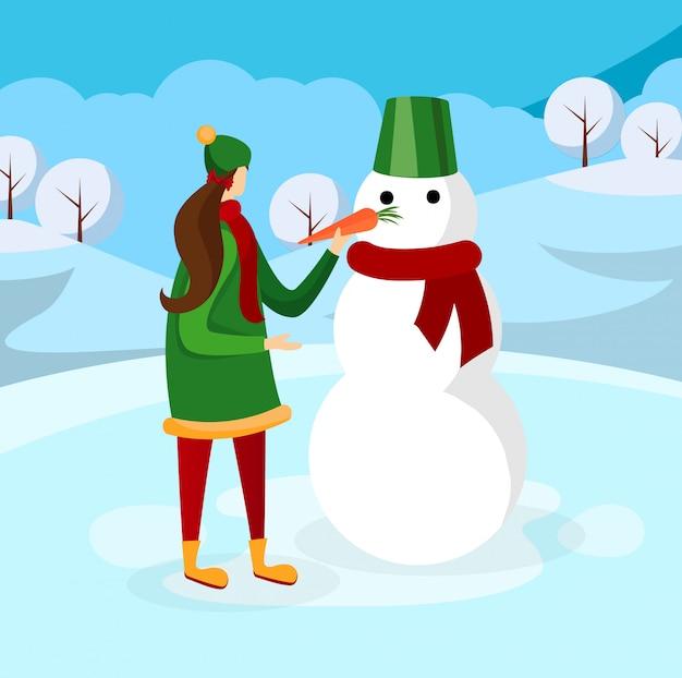 Nettes mädchen, das schneemann auf winter-hintergrund macht