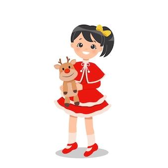 Nettes mädchen im weihnachtskostümkleid, das eine rentierpuppe hält. flache zeichentrickfigur lokalisiert im weißen hintergrund.