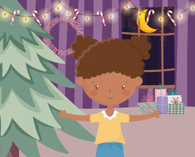 Nettes mädchen mit zuckerstangengeschenken der hellen lichter des baums frohe weihnachten
